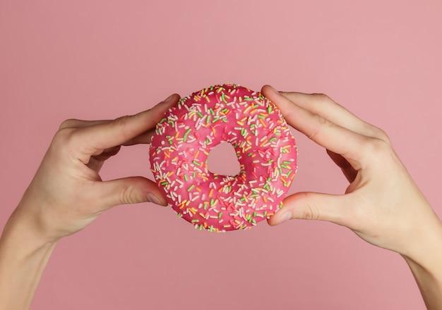 Женские руки, держа глазированные пончик на розовом фоне. тенденция пастельных тонов. похудела после отпуска. вид сверху.