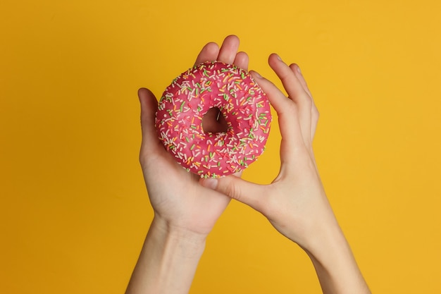 Female hands holding a glazed donut on yellow background. sweet dessert. top view.