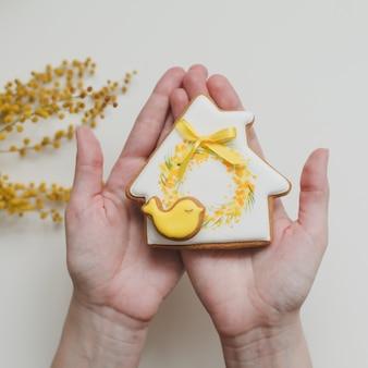 白い背景に艶をかけられたジンジャーブレッドクッキーを保持している女性の手。春、ハッピーイースターのコンセプト。上面図