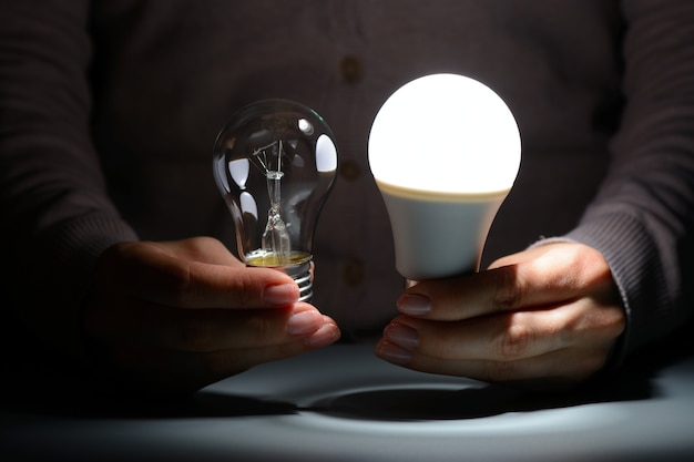 Female hands holding a glowing led and incandescent bulbs in the dark
