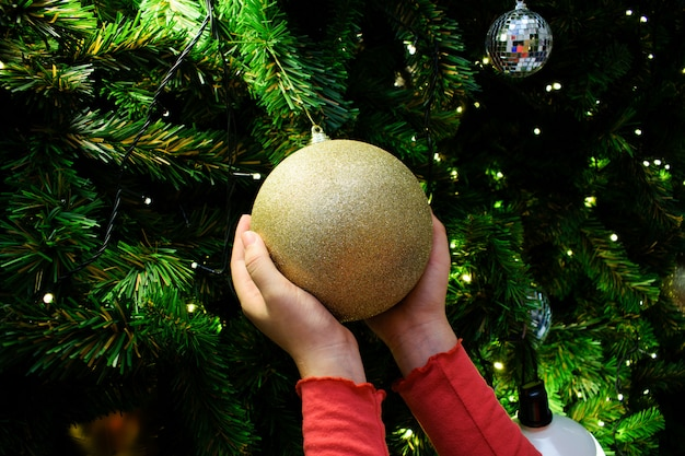 Female hands holding a golden ball. decorated christmas tree in silver and gold theme.
