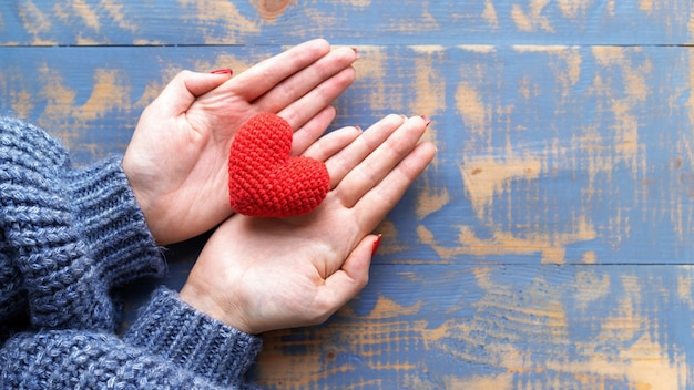Female hands holding a handmade knitted red heart. top view