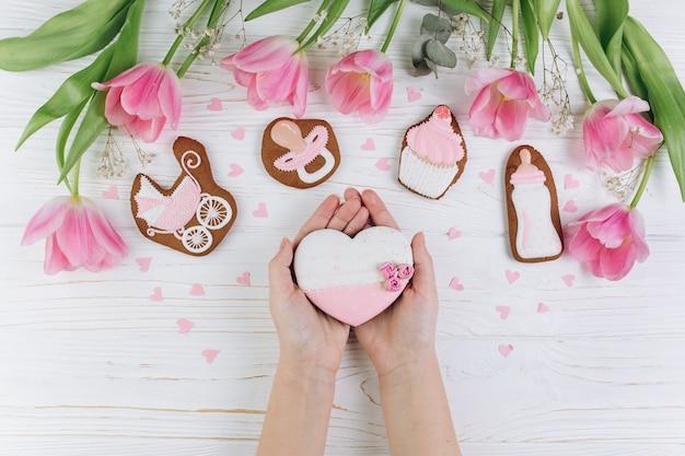 女性の手が心臓を保持します。木製の白い背景に新生児のための組成物。
