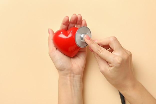 Женские руки держат сердце и стетоскоп на бежевой поверхности
