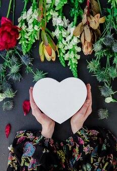 어두운 표면에 꽃 근처 하트 모양 선물 상자를 들고 여성 손