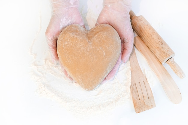 ハート型の生地の上面図を保持している女性の手。白いテーブルの上の材料を焼く