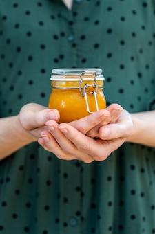 Mani femminili che tengono una marmellata di albicocche cruda vegana fatta in casa in un barattolo di vetro