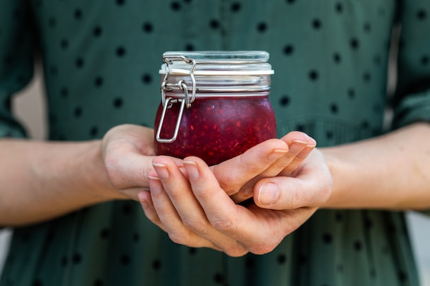 Female hands holding a homemade vegan raw raspberry jam in a glass jar