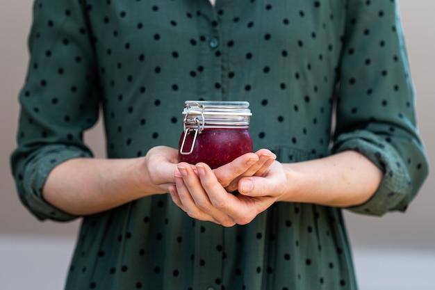 Mani femminili che tengono una marmellata di lamponi cruda vegana fatta in casa in un barattolo di vetro