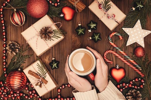 Женские руки держат чашку горячего кофе на деревянном столе с рождественскими украшениями