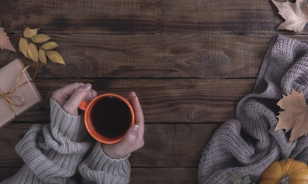 Female hands holding hot coffee on wooden background