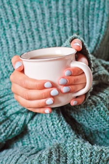 Female hands holding hot cup of coffee or tea.