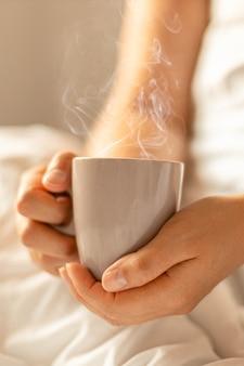 이른 아침에 침대에 앉아있는 동안 아로마 음료 커피 또는 차와 뜨거운 컵을 들고 여성 손. 수직 비디오