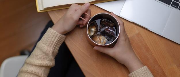 ノートパソコンと本と木製の作業台にアイスコーヒー・マグを保持している女性の手