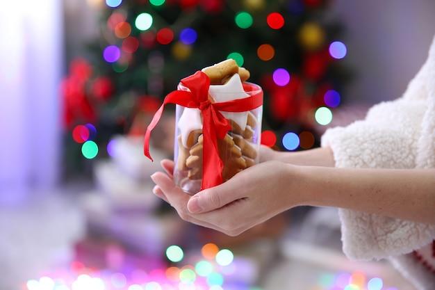 クリスマスのクッキーと瓶を保持している女性の手