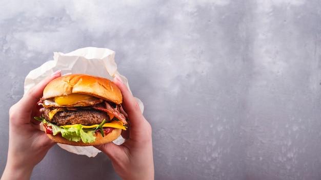 Женские руки, держа сочный говяжий бургер с жареным яйцом. вид сверху. быстрое питание. стиль жизни. копировать пространство