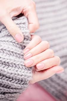Женские руки, держа большой серый шерстяной шарф.