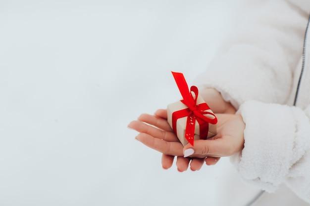 白い壁に小さなギフトボックスを保持している女性の手。冬の休日、バレンタインデーの概念。