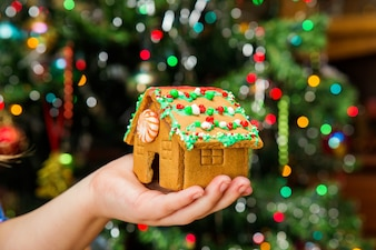 Female hands holding little gingerbread house on table with Christmas decorations.