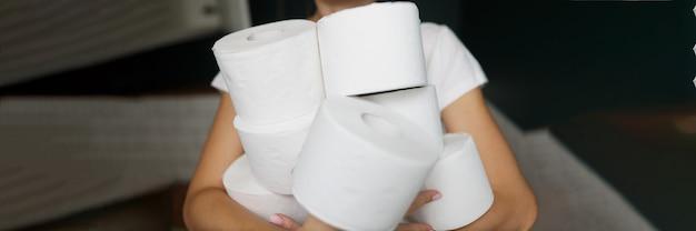 白いトイレットペーパーのクローズアップの多くのロールを保持している女性の手