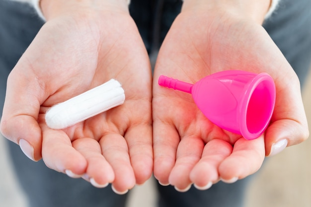 여성의 손에 생리 컵과 의료 탐폰을 들고