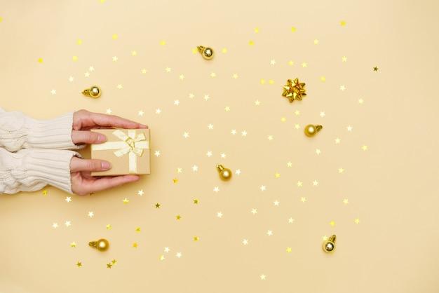 黄色の装飾が施された休日の背景の女性の準備にメリークリスマスギフトボックスを保持している女性の手...