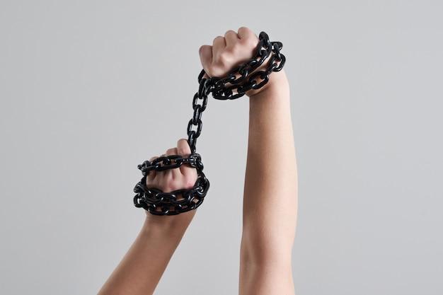 Женские руки держат металлическую металлическую цепь над головой