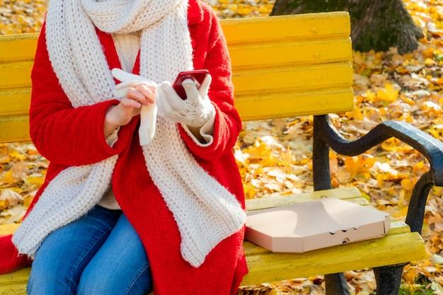 ピザとパッケージボックスの近くで携帯電話を保持している女性の手。