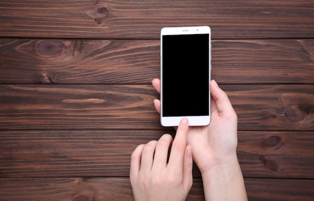 Female hands holding mobile phone with blank screen