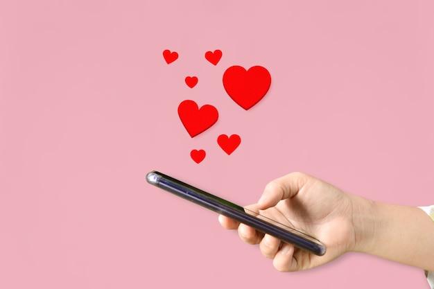 여성의 손에 마음, 분홍색 배경에 사랑 상징으로 휴대 전화를 들고. 발렌타인 데이 개념.