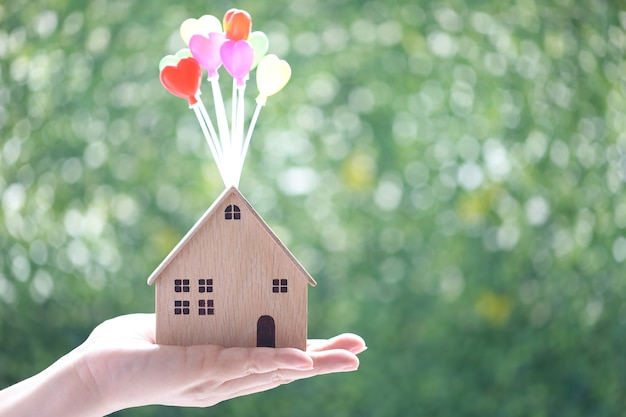 Female hands holding model house with balloon on natural green background, save money for prepare in future and banking concept