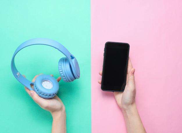 Female hands holding a modern smartphone and headphones on a pastel background