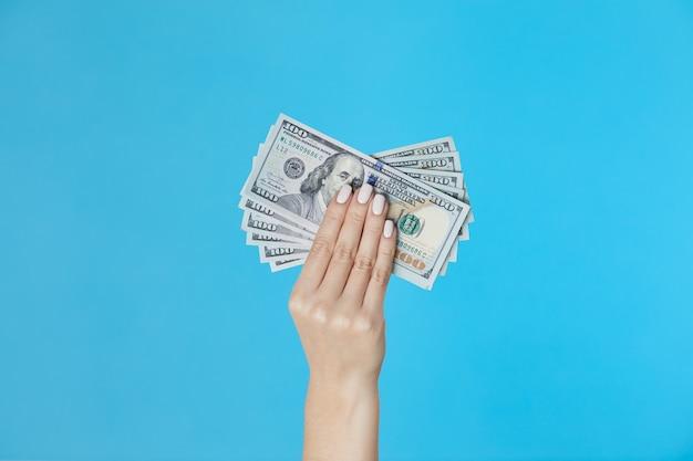 Female hands holding money on blue