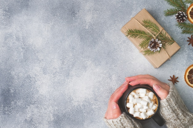 Female hands holding a mug with hot chocolate and marshmallows on gray