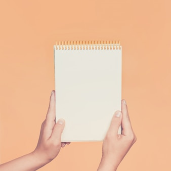 Female hands holding open a blank notepad for notes on the peach wall. toned.