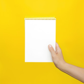Female hands holding open a blank notepad for notes on the yellow.