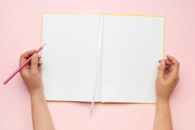 ピンクの背景にきれいなシートで開いたメモ帳を保持している女性の手