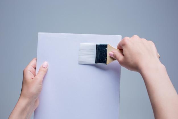 白いキャンバスに絵筆を持っている女性の手