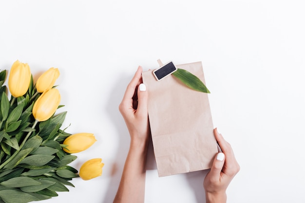 Female hands holding a paper bag with a gift near the bouquet of yellow tulips on a white background