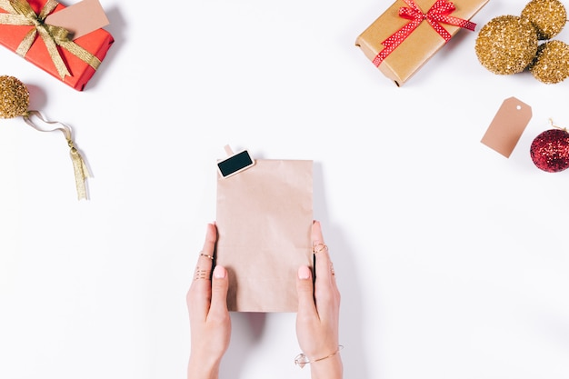 Female hands holding a paper bag with a new year's gift
