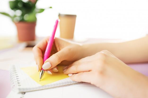 ペンを持つ女性の手。トレンディなピンクの机の上の電話。