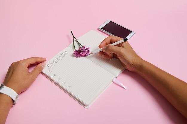 여성의 손은 연필을 잡고, 공책에 쓰고, 할 일 목록을 확인합니다. 휴대 전화와 분홍색 꽃은 복사 공간이 있는 분홍색 배경에 놓여 있습니다. 비즈니스, 계획 및 시간 관리 개념