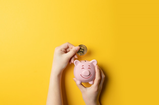 Female hands holding piggy piggy bank and putting bitcoin money in the piggy bank.