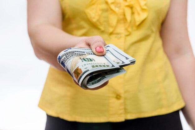 ドル紙幣の山を保持している女性の手がクローズアップ