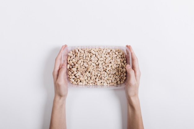 Female hands holding a plastic container with roasted peanuts on a white background