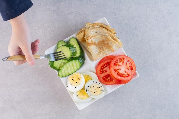 石のテーブルで朝の朝食とプレートを保持している女性の手。