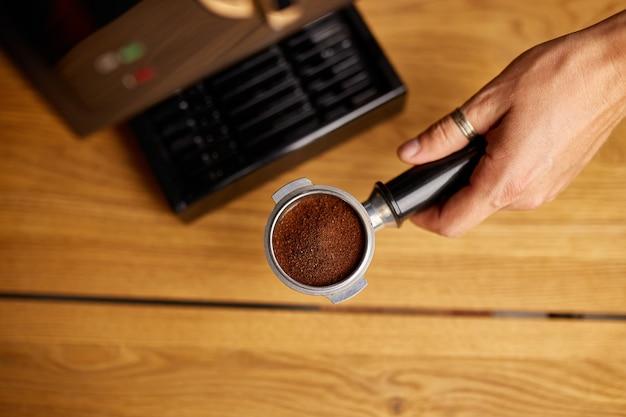 ポルタフィルターを持って、モダンなコーヒーメーカーを使用して自宅で新鮮なアロマコーヒーを作る女性の手、モダンなカフェで挽いたコーヒーメーカーからエスプレッソを作る男性のバリスタ