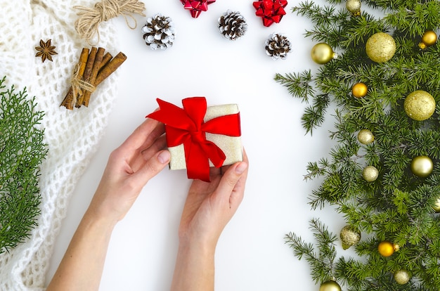 Female hands holding present, fir tree,gold balls. holidays: christmas, new year.