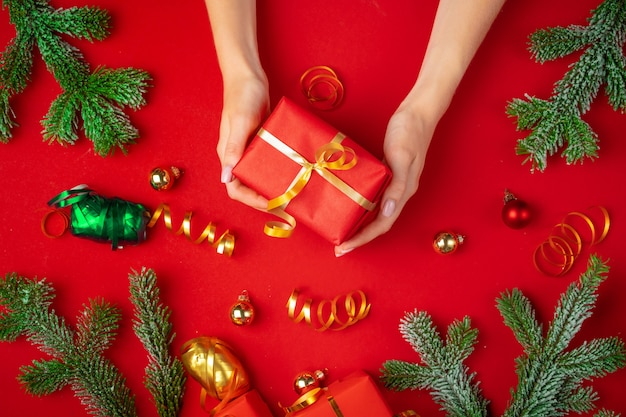 Female hands holding present on a red background
