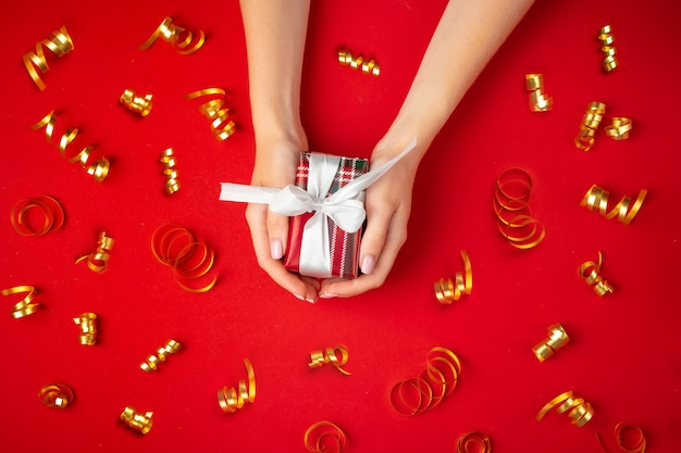 Female hands holding present on a red